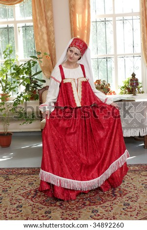 The girl poses in red old russian dress - stock photo