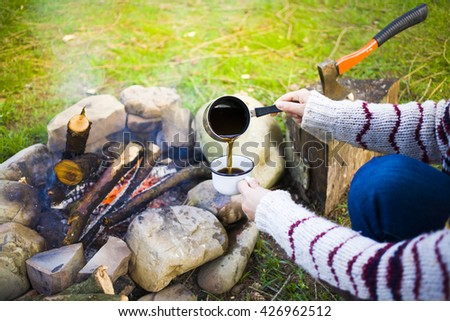 The girl prepares coffee by the fire in nature in the camping.