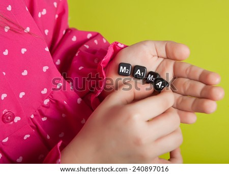 The girl puts on the palm of chips the word Mama on a green background - stock photo