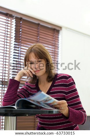 The girl reads magazine in cafe - stock photo