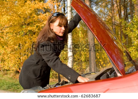 The girl repairs the car motor - stock photo