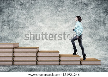 The girl rises upwards on a ladder from books - stock photo