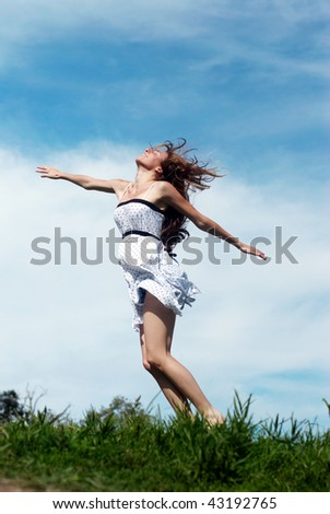 The girl running on a grass against the sky