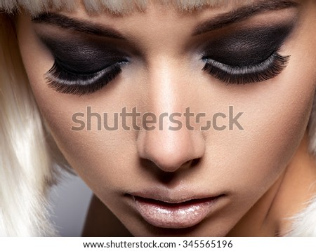 The girl's face closeup with long black lashes. fashion makeup - stock photo