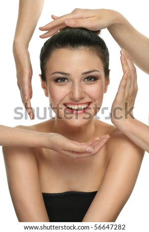 The girl's face is surrounding with caring hands of experts - care of beauty and health