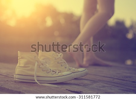 The girl's legs and sneakers - stock photo