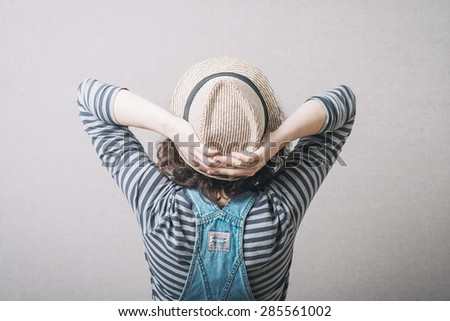 the girl sat in a hat, rear view dressed in overalls - stock photo