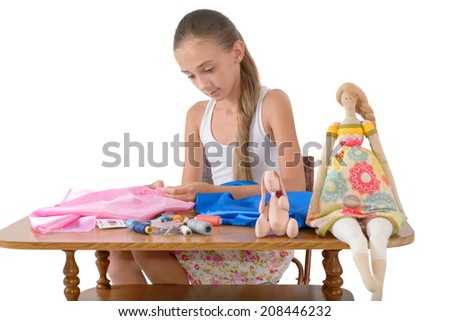 The girl sews toys from fabric on the white background - stock photo