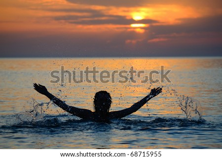 The girl sharply lifts hands from water. Decline. Silhouette. - stock photo
