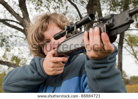 The girl Shooting from a gun. Training shooting from an air rifle in the autumn afternoon - stock photo