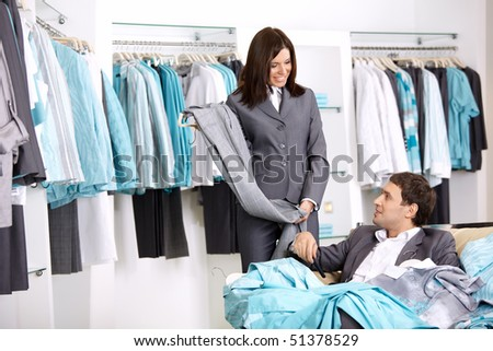 The girl shows to the man trousers chosen in shop - stock photo