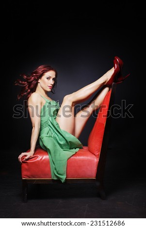 the girl sits in a beautiful pose on a armchair - stock photo