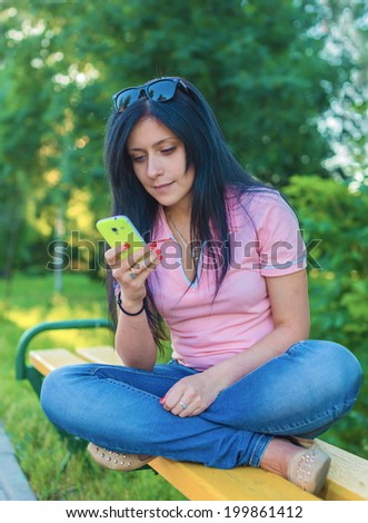 The girl sits on a bench and looks at phone - stock photo