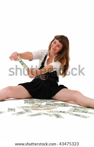 The girl sits on a floor and looks at a banknote. Isolate on  white