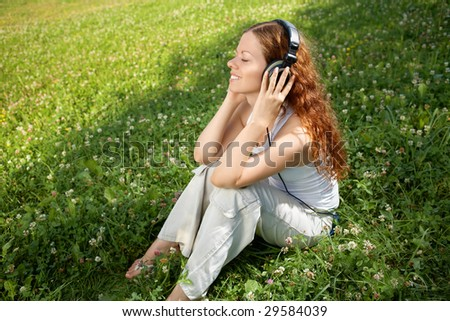 The girl sits on a meadow and listens to music in ear-phones