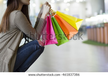 The girl sitting holding shopping bags in the mall.