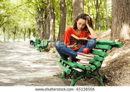 The girl sitting on a bench, reading a book - stock photo