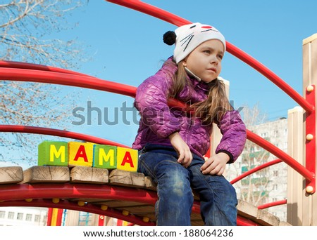 The girl sitting on the children's bridge with cubes with the word mother in Russian - stock photo