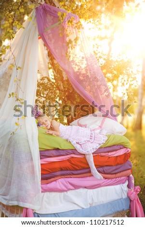"the girl sleeps on a bed. the fairy tale ""the princess on a pea"" - stock photo"