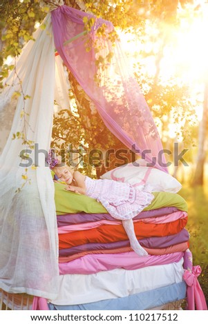 "the girl sleeps on a bed. the fairy tale ""the princess on a pea"""