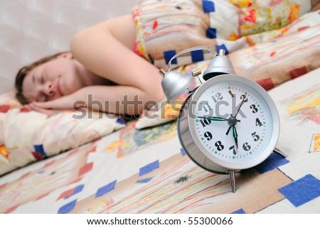The girl sleeps. The alarm clock nearby lays - stock photo