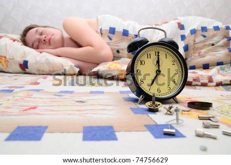 The girl sleeps. The broken alarm clock nearby lays - stock photo