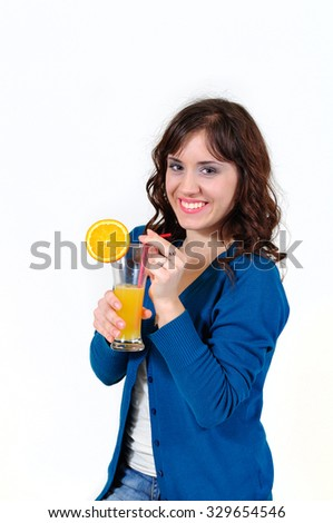 The girl smiles and drinks juice on a white background - stock photo