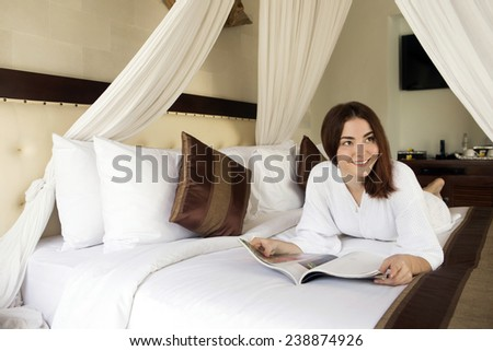 The girl smiles keeping magazine lying on a bed.