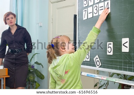 The girl solves an example at a board, - stock photo