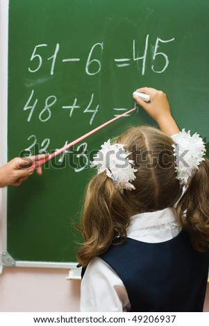 The girl solves examples at a lesson at a school board - stock photo