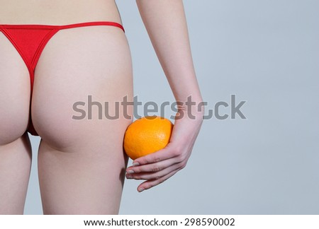 The girl stand back on a white background and holds orange - stock photo