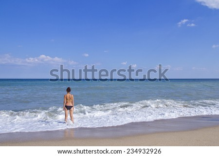 The girl standing on the sea shore \ The silhouette of the girl on the beach - stock photo