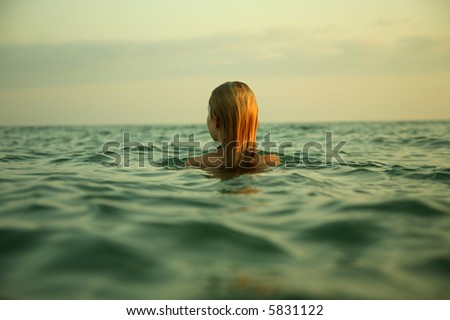 The girl swiming in sea waves. An art photo. A beautiful landscape. - stock photo