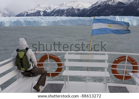 The girl, The banner of Argentina  and Perito Moreno Glacie - stock photo