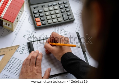 The girl the designer, architect, business woman makes calculations, drawing drawings, diagram, writes the formula on a wooden table with blueprints, toy house and calculator