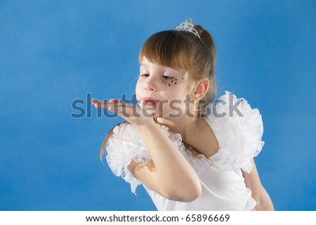 The girl the princess in a white dress sits opposite to a blue background