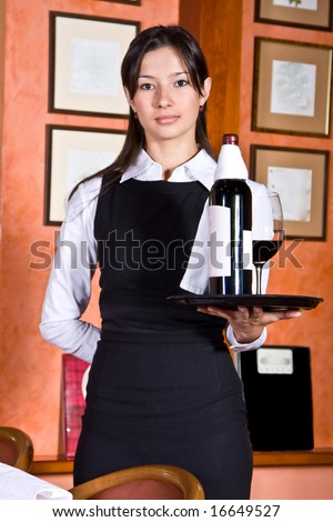 The girl the waiter with a tray on which bottle red wine and a wine-glass