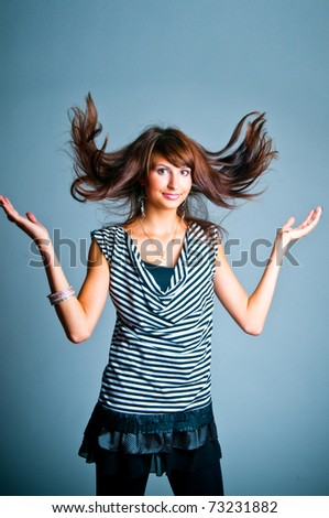 The girl throws hair on a gray background - stock photo