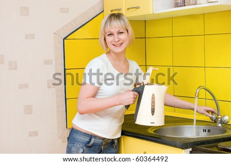 The girl types water in a teapot - stock photo