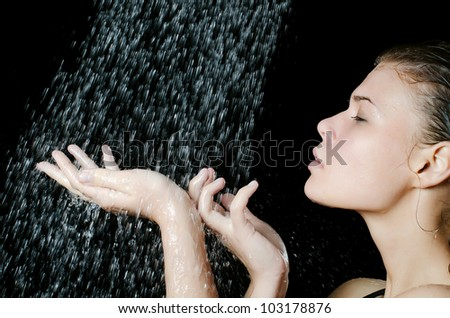 The girl under a shower on black - stock photo