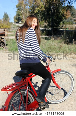 The girl who riding a red bicycle