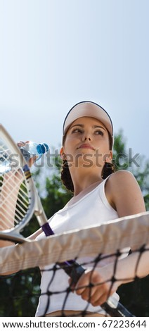 The girl-winner looks at the competitor on tennis & drink water - stock photo