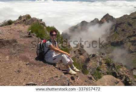 The girl with a backpack sits has a rest on a stony track highly in mountains, at the level of clouds in the summer afternoon
