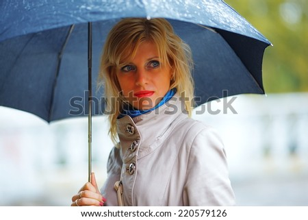 the girl with a black umbrella costs in the rain - stock photo