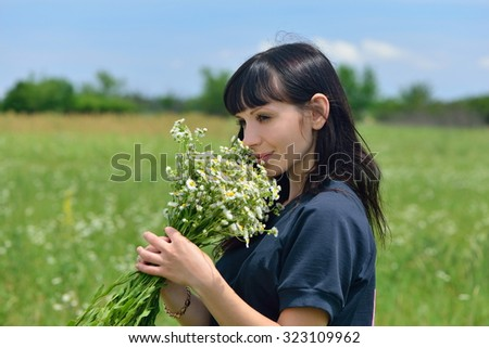 The girl with a bouquet of wild flowers in the field - stock photo