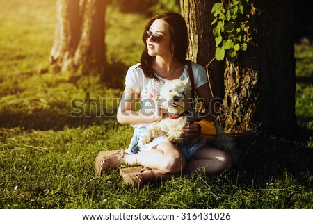 The girl with a dog sit on a grass under the tree - stock photo