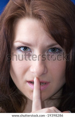 The girl with a finger near a mouth on a blue background. Asks silences