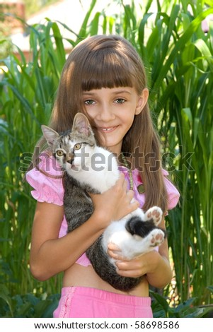 The girl with a kitten on a background of a green bush