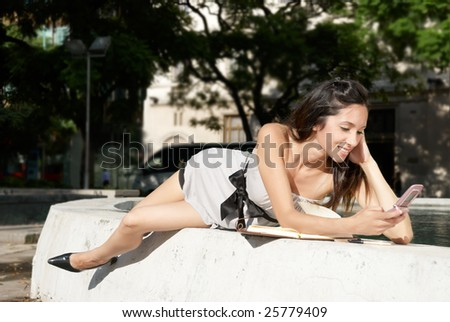The girl with a mobile phone near a fountain - stock photo