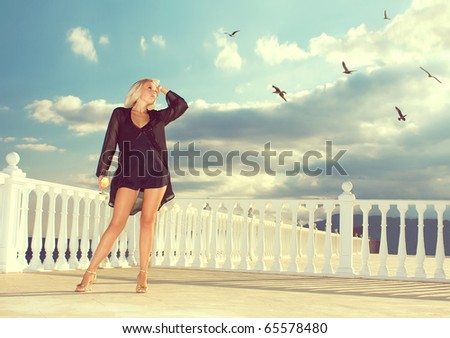 The girl with a wine glass looks at birds - stock photo